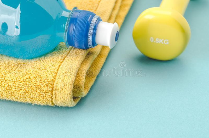 Fitness concept with dumbbell, towel and bottle/yellow dumbbell, towel and bottle on a blue background. selective focus royalty free stock photography