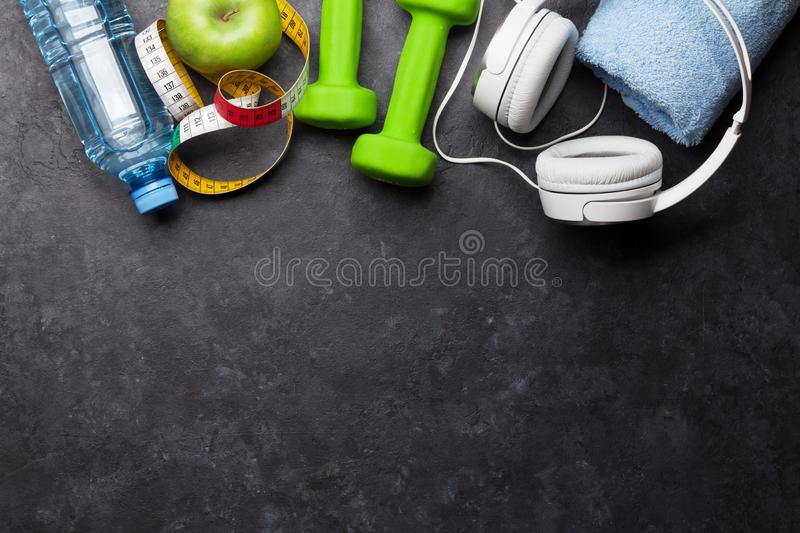 Fitness concept. Dumbbells, headphones and apple royalty free stock images