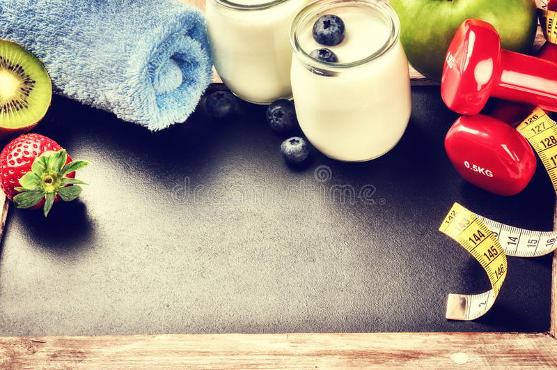 Fitness concept with dumbbells and healthy food. Copy space royalty free stock photo
