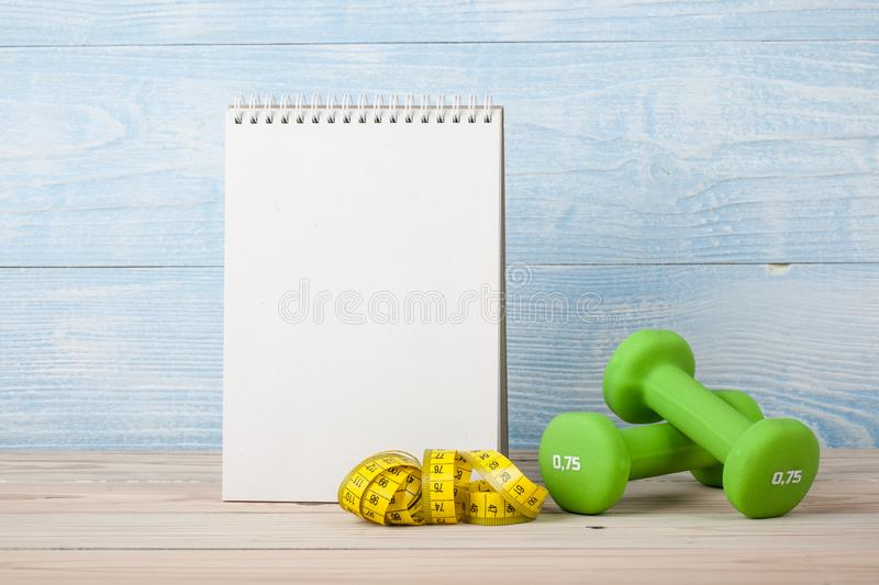 Fitness concept with dumbbells and notepad for workout plan. Copy space stock images
