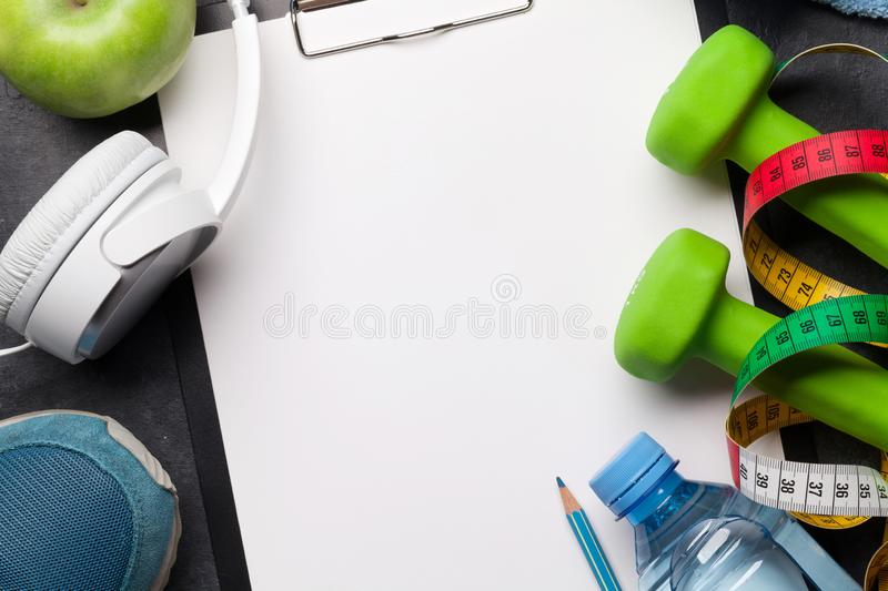 Fitness concept. Dumbbells, sneakers, headphones and apple stock photography