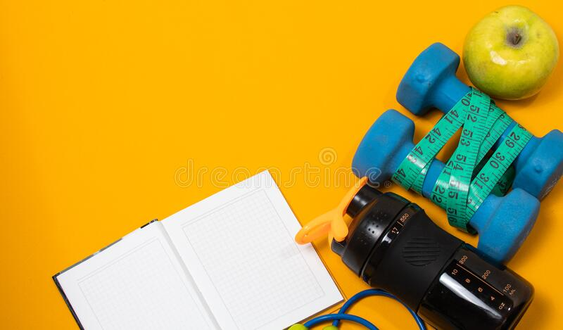 Fitness concept flatlay banner with dumbbells, jump ropes and measuring tape. On a yellow background stock photo