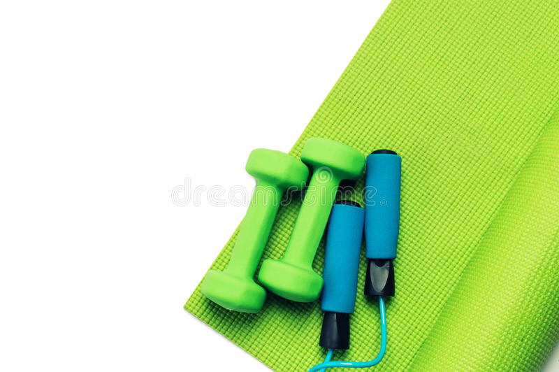 Fitness concept - green yoga mat, dumbbells and skipping rope. On the white background royalty free stock photo