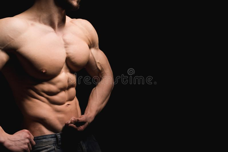 Fitness concept. Muscular and fit torso of young man having perfect abs, bicep and chest. Male hunk with athletic body. On black background. Copypaste space royalty free stock images