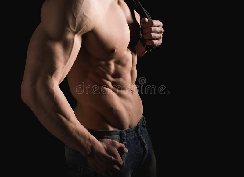 Fitness concept. Muscular and fit torso of young man having perfect abs, bicep and chest. Male hunk with athletic body. On black background. Copypaste space stock photography