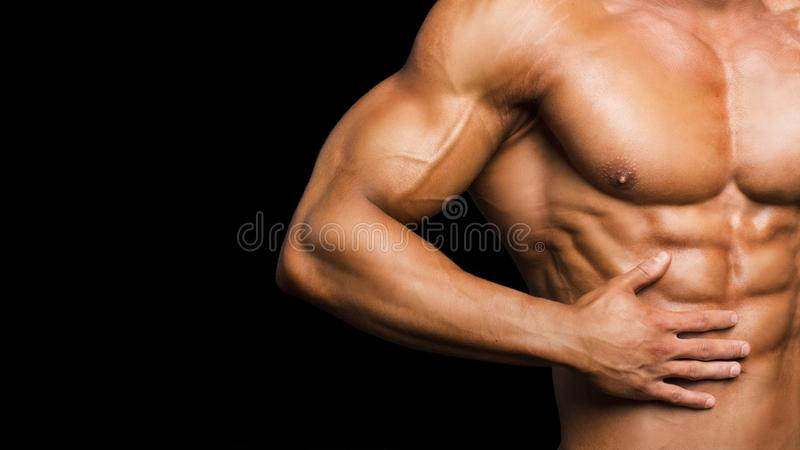 Fitness concept. Muscular and fit torso of young man having perfect abs, bicep and chest. Male hunk with athletic body. On black background royalty free stock photos
