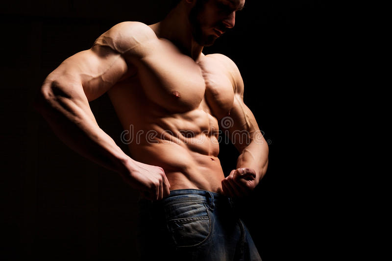 Fitness concept. Muscular and torso of young man having perfect abs, bicep and chest. Male hunk with athletic body. Muscular and torso of young man having stock image