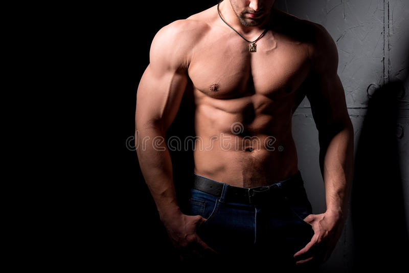 Fitness concept. Muscular and torso of young man having perfect abs, bicep and chest. Male hunk with athletic body. Muscular and torso of young man having stock photography