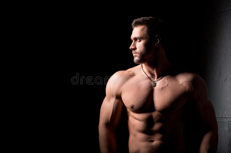 Fitness concept. Muscular and torso of young man having perfect abs, bicep and chest. Male hunk with athletic body. Muscular and torso of young man having royalty free stock photos