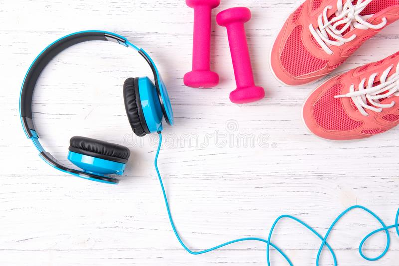 Fitness concept with pink sneakers, dumbbells and blue headphones on wooden background, top view royalty free stock photo