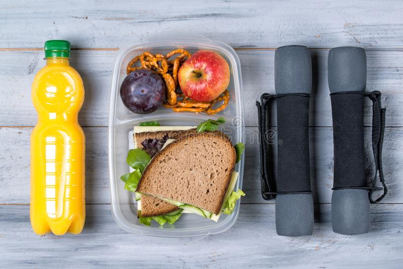 Fitness concept, sandwich and fruits to go, orange juice and dumbbells, wooden background, top view royalty free stock image