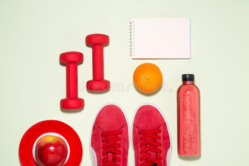 Fitness concept. Sneakers, apple, dumbbell and fruit juice bottle on pastel color background. royalty free stock image