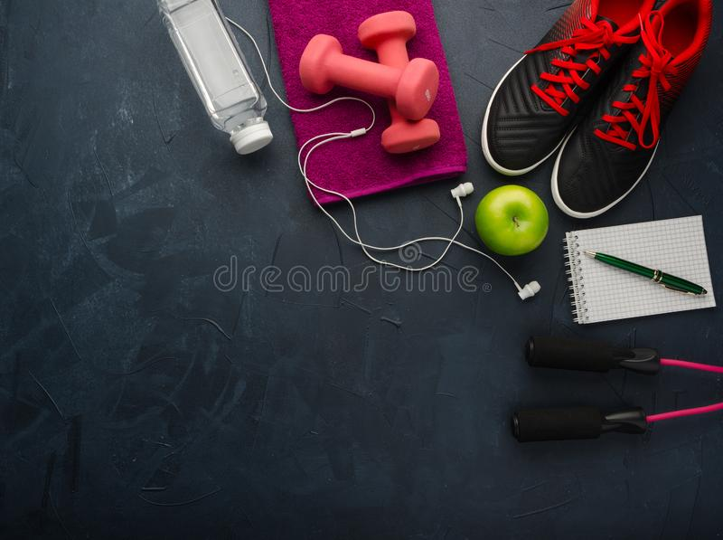 Sneakers dumbbells bottle of water apple and skipping rope. Fitness concept with sneakers dumbbells bottle of water apple and skipping rope on black concrete royalty free stock photos