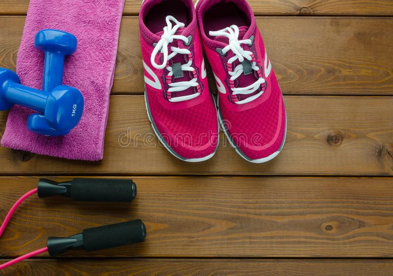 Sneakers dumbbells towel and Skipping rope on wooden table background. Fitness concept with sneakers dumbbells towel and Skipping rope on wooden table background stock photo