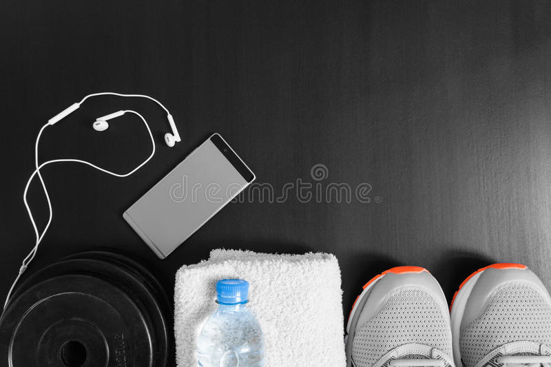 Fitness concept. Sport equipment. Sneakers sport shoes, towel, bottle of water, earphones, dumbbells and phone on black backgrou royalty free stock photography