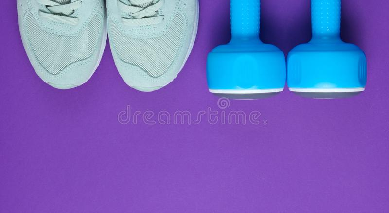 Fitness concept. Sports sneakers, blue plastic dumbbells on a purple background. Top view. Copy space. Fitness concept. Sports sneakers, blue plastic dumbbells royalty free stock image