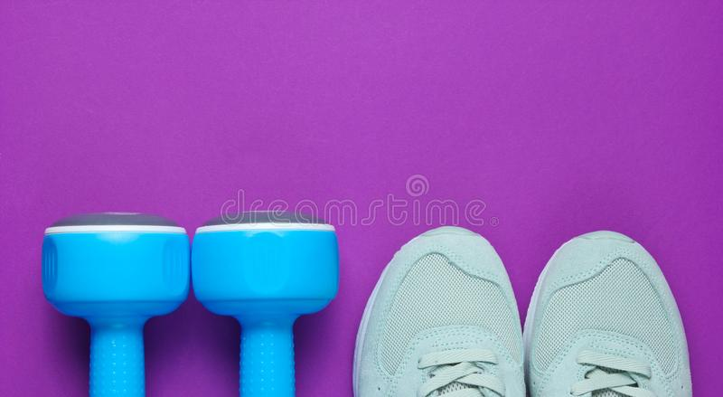 Fitness concept. Sports sneakers, blue plastic dumbbells on a purple background. Top view. Copy space royalty free stock images
