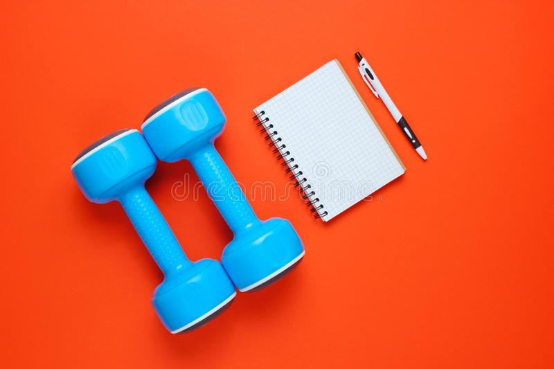 Fitness concept, workout plan. Plastic blue dumbbells, notepad on orange background. Top view. Flat lay. stock images