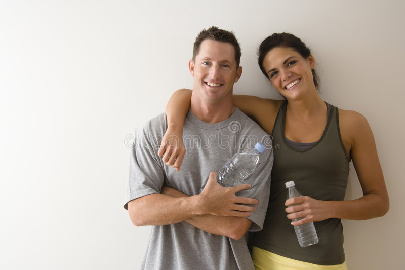 Fitness couple. Man and woman at gym in fitness attire holding water bottles standing against wall smiling
