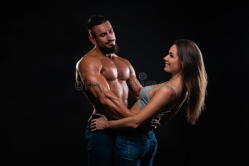 Fitness couple on a black background are in the studio stock images