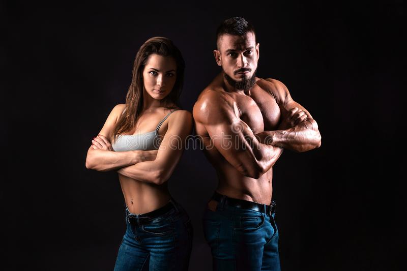 Fitness couple on a black background looking to the camera with crossed arms royalty free stock photography