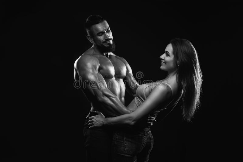 Fitness couple on a black background are in the studio. Black and white stock image