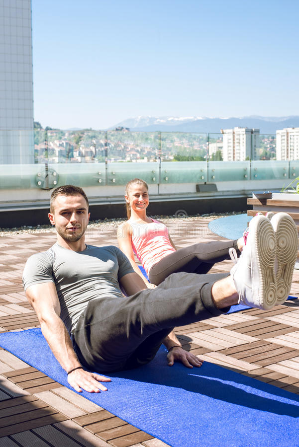 Fitness couple doing legs up crunches stock photos
