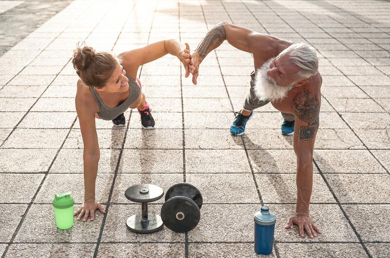 Fitness couple doing push ups exercise outdoor - Happy athletes making workout session outside stock images