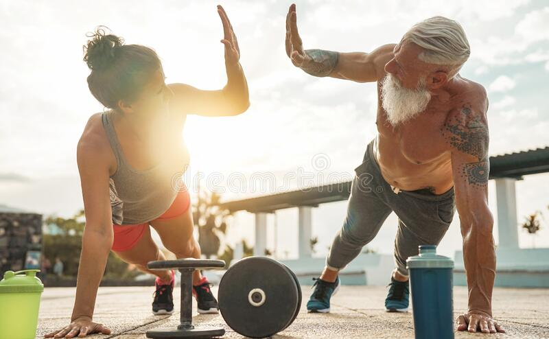 Fitness couple doing push ups exercise at sunset outdoor - Happy athletes making gym workout session outside royalty free stock photo