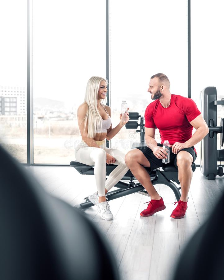 Fitness couple drinking water in gym stock image