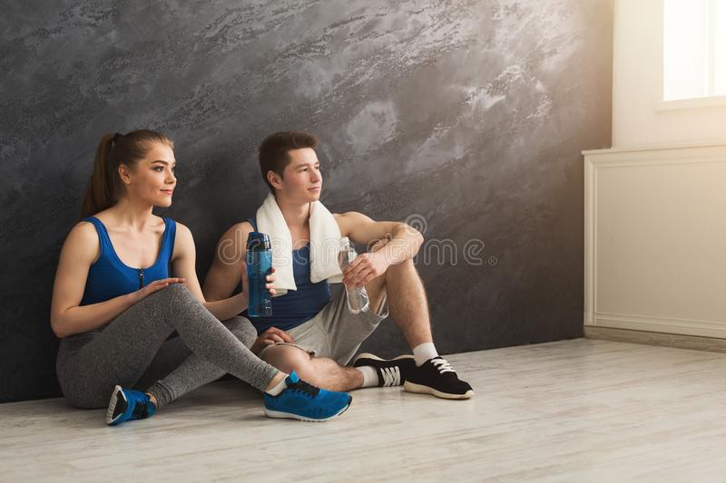 Fitness couple drinking water at gym royalty free stock photo