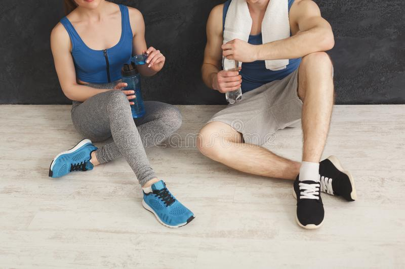 Fitness couple drinking water at gym stock photography