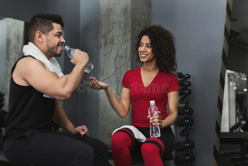 Fitness couple having rest and talking at gym royalty free stock images
