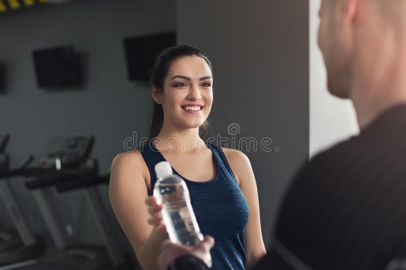 Fitness couple sharing water at gym royalty free stock image