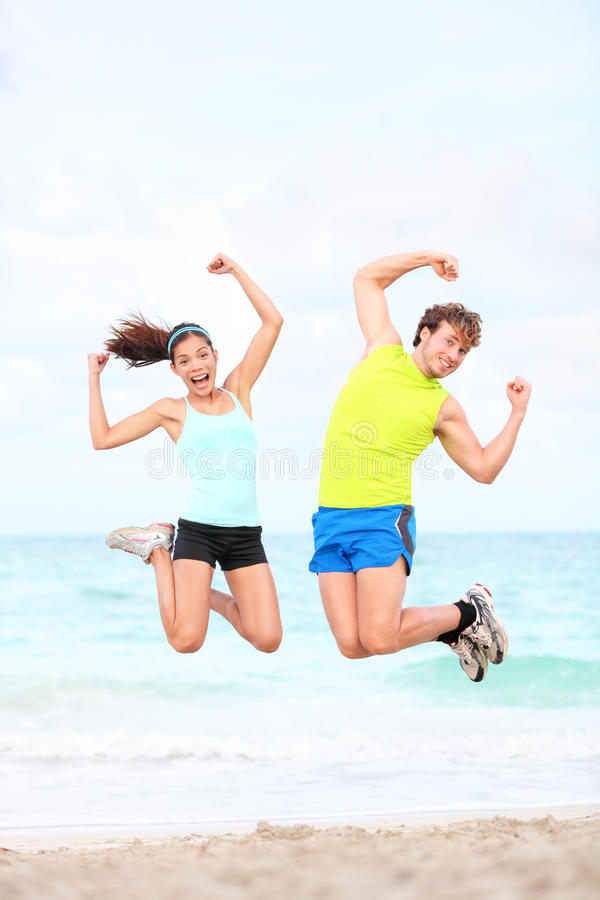 Fitness couple jumping fun stock photo