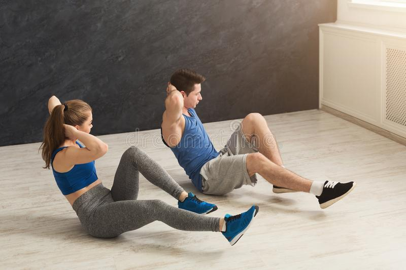 Fitness couple lying doing crunches stock images