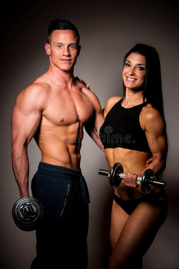 Fitness couple poses in studio - fit man and woman stock image