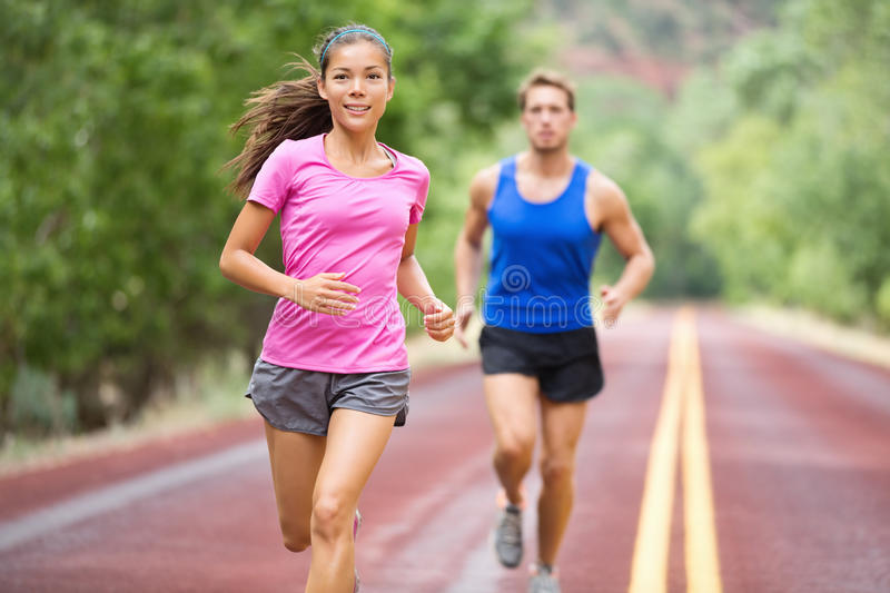 Fitness couple running training outside on road royalty free stock image