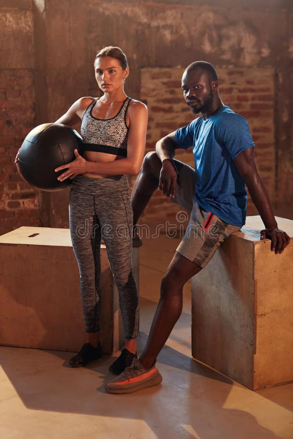 Fitness couple in sport clothes after workout at gym portrait. Fit people in sportswear with med ball after functional training indoors stock photos