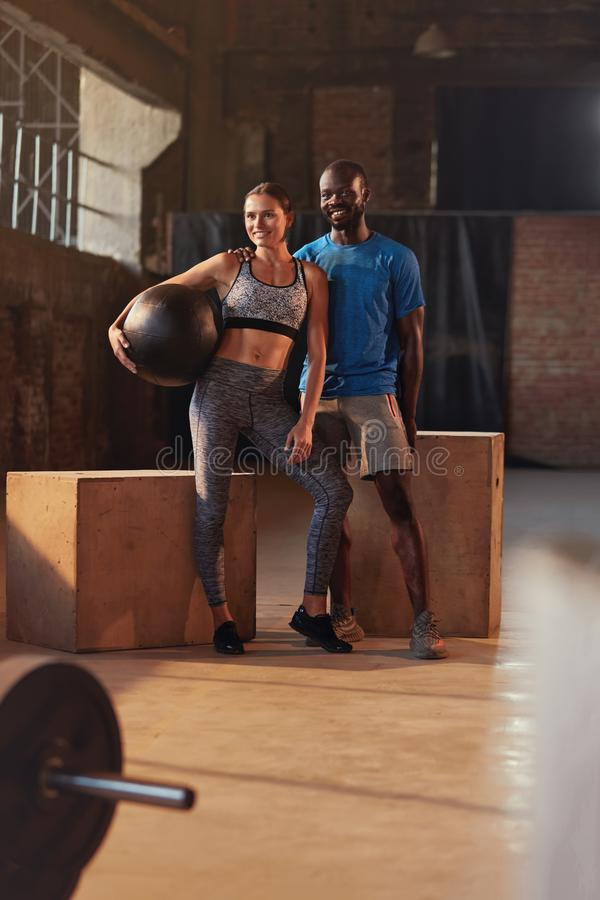 Fitness couple in sport clothes after workout at gym portrait. Fit people in sportswear with med ball after functional training indoors royalty free stock photography