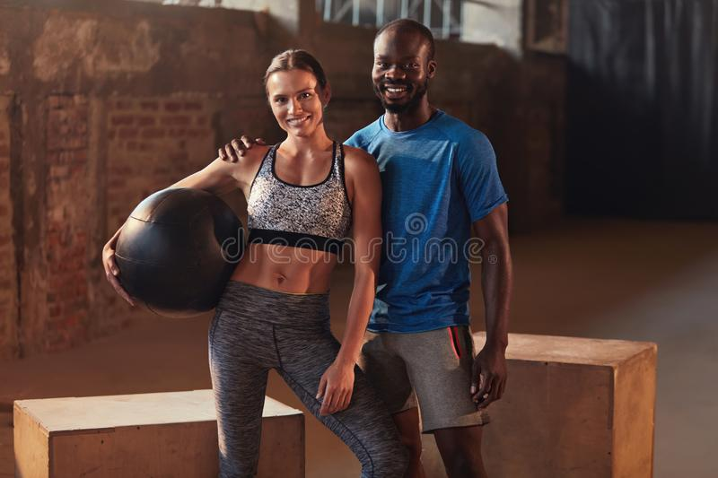 Fitness couple in sport clothes after workout at gym portrait. Fit people in sportswear with med ball after functional training indoors royalty free stock photos