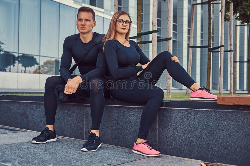 Fitness couple in a sportswear, blonde girl and a handsome muscular guy sitting on a bench against a skyscraper. stock images