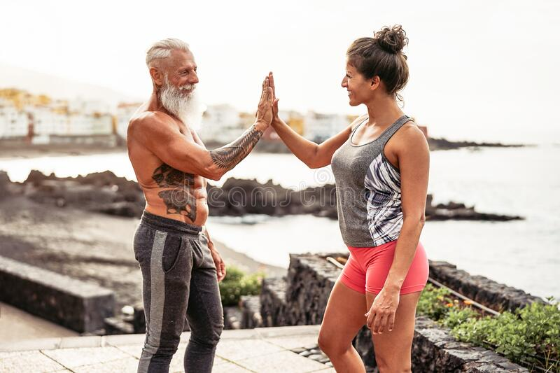Fitness couple stacking hands during a workout day outdoor - Happy athletes motivating each other royalty free stock images