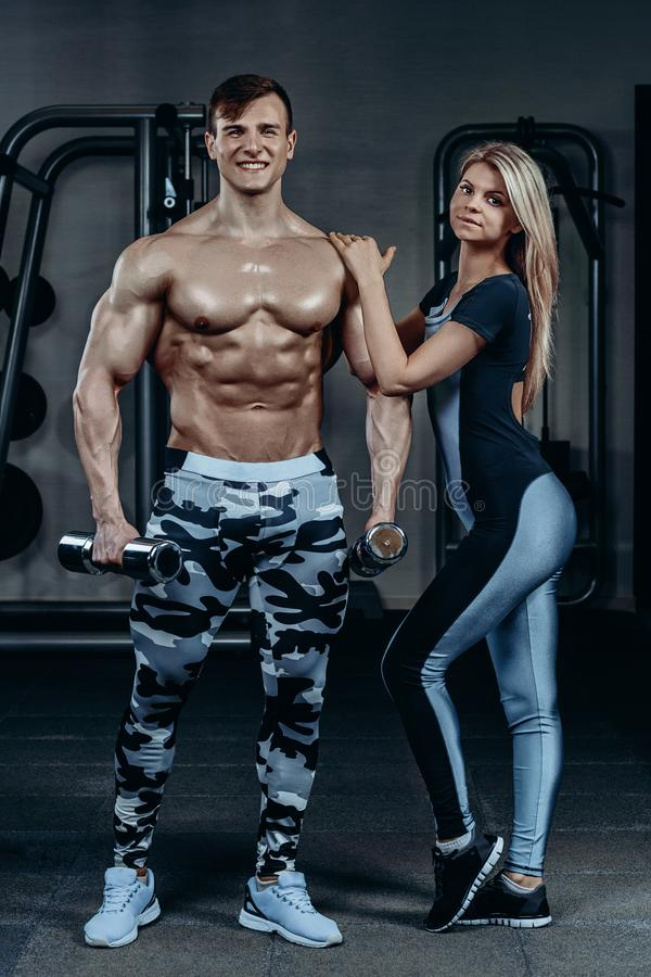 Fitness couple - woman and man with dumbbells in gym royalty free stock image