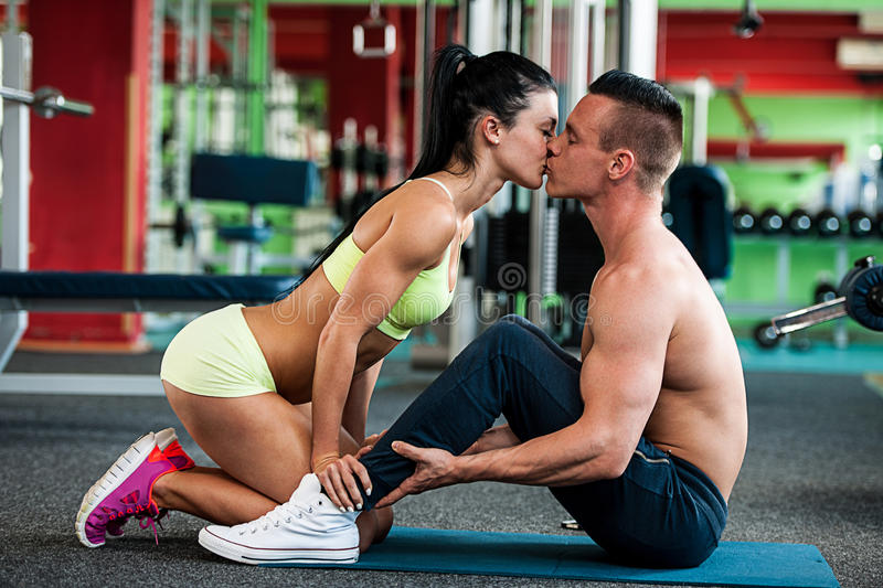 Fitness couple workout - fit man and woman train in gym royalty free stock image