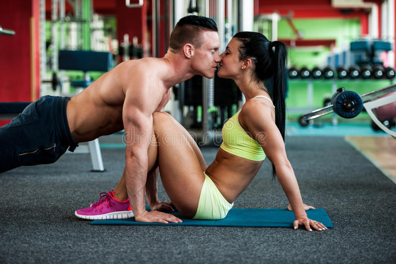 Fitness couple workout - fit mann and woman train in gym royalty free stock photo