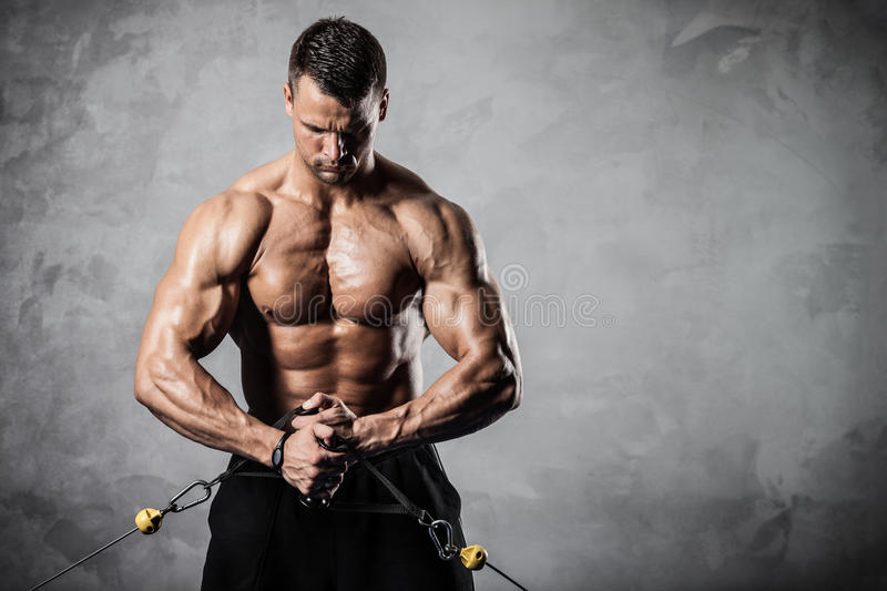 Fitness on crossover. Brutal athletic man pumping up muscles on crossover royalty free stock image