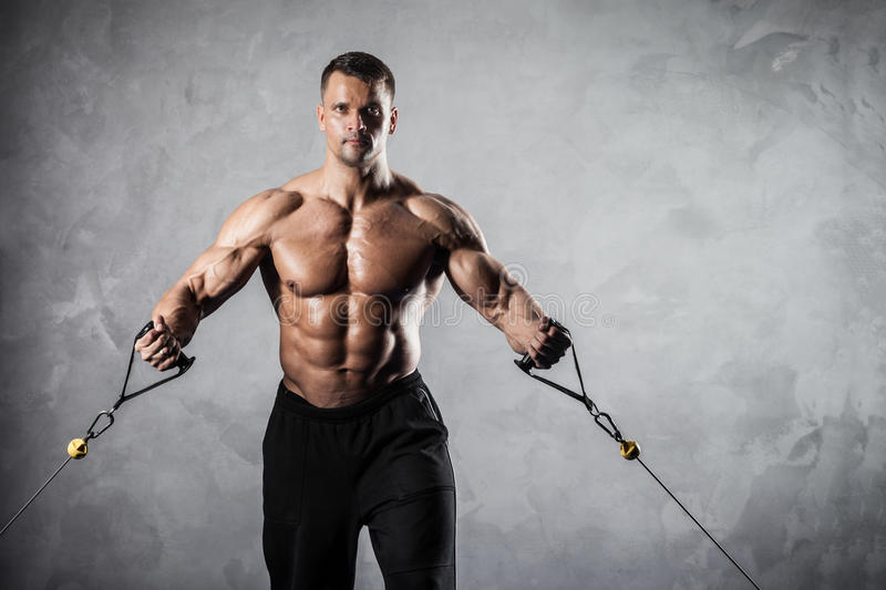 Fitness on crossover. Brutal athletic man pumping up muscles on crossover stock image