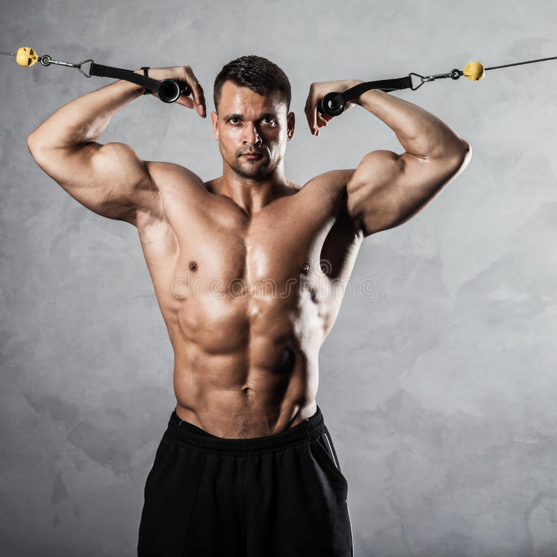 Fitness on crossover. Brutal athletic man pumping up muscles on crossover stock images