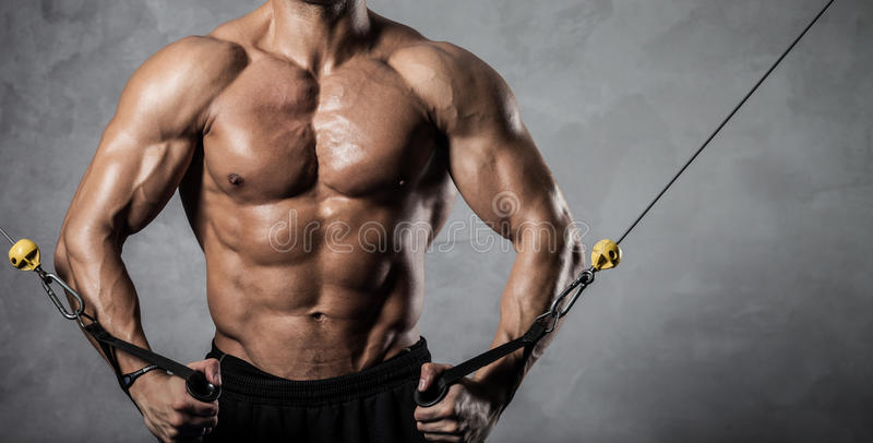 Fitness on crossover. Brutal athletic man pumping up muscles on crossover royalty free stock photo